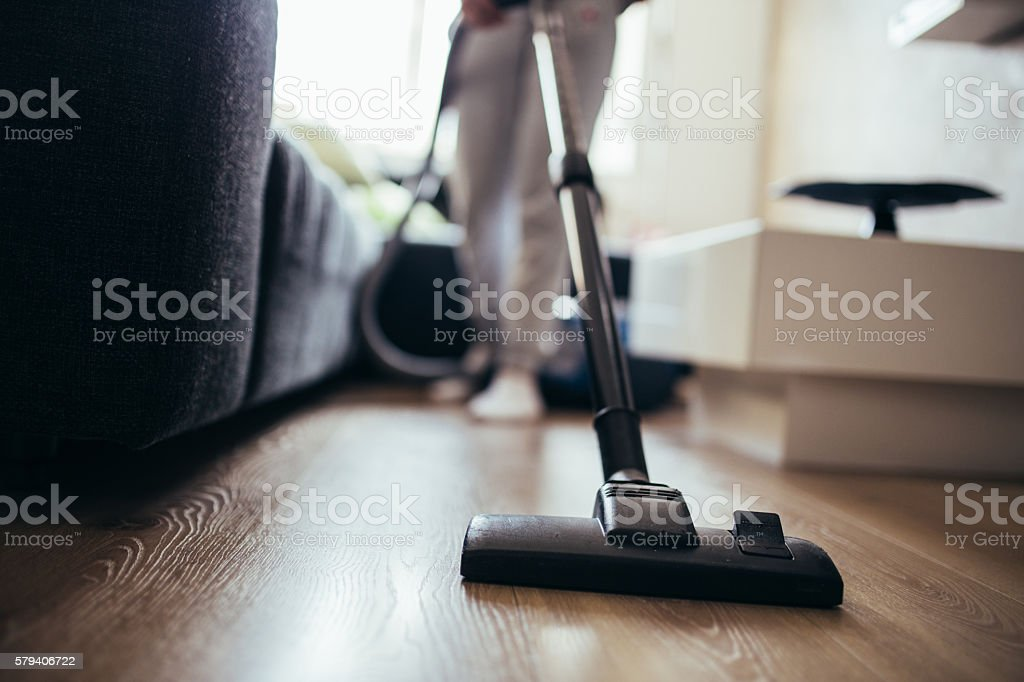Woman cleaning the floor in living room with vacuum cleaner. cropped...