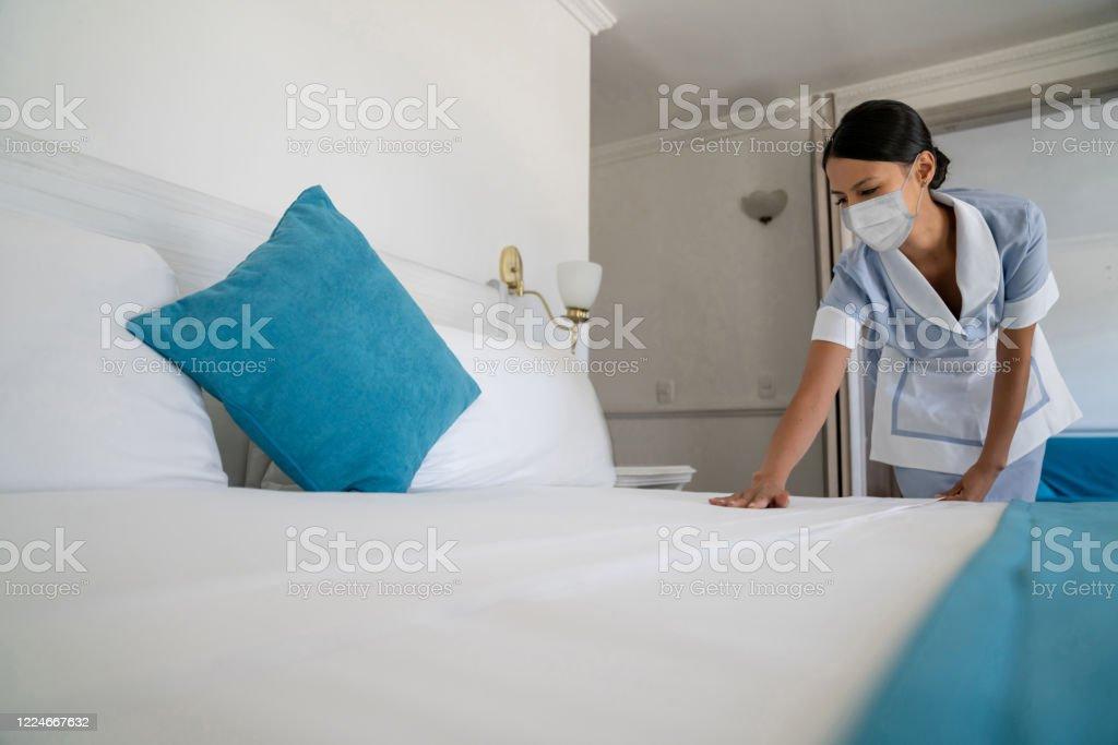 Magd, die das Bett mit einer Gesichtsmaske trägt, während sie in einem Hotel arbeitet - Lizenzfrei Ansteckende Krankheit Stock-Foto