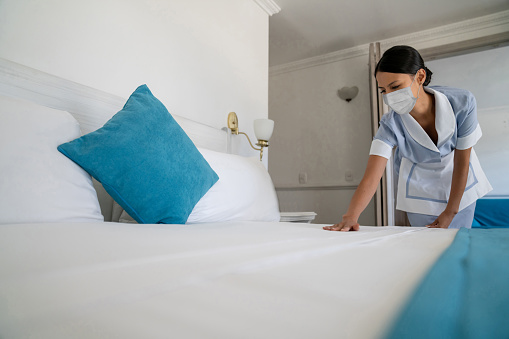 Maid doing the bed wearing a facemask while working at a hotel