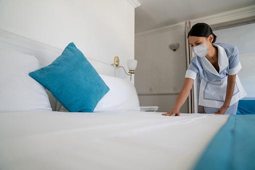 Magd Die Das Bett Mit Einer Gesichtsmaske Trägt Während Sie In Einem Hotel Arbeitet Stockfoto und mehr Bilder von Ansteckende Krankheit