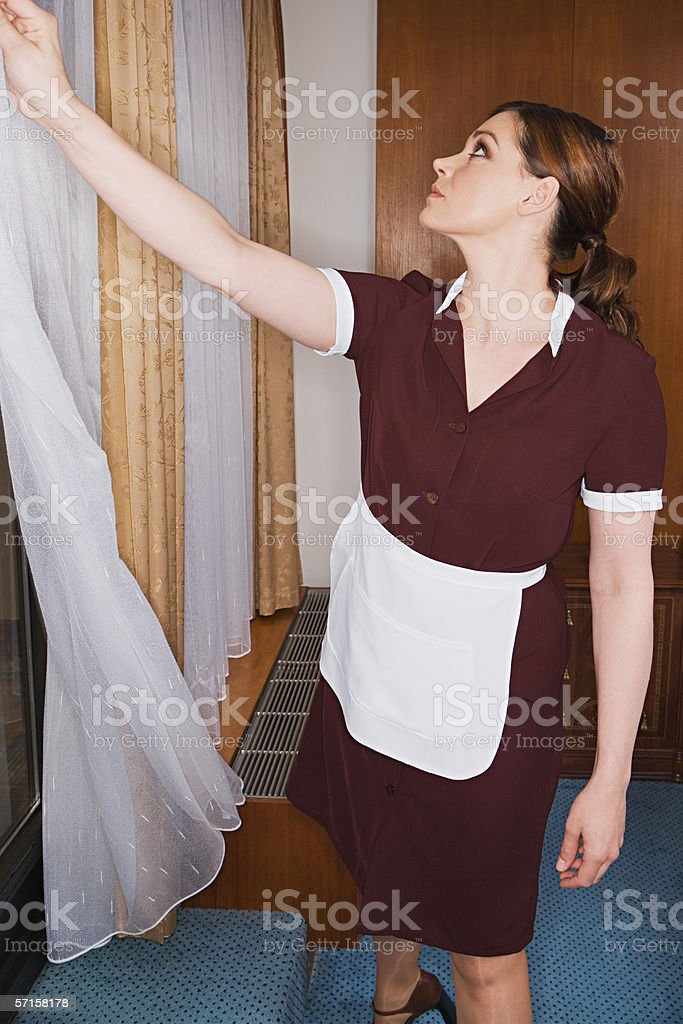 Maid drawing curtain royalty-free stock photo