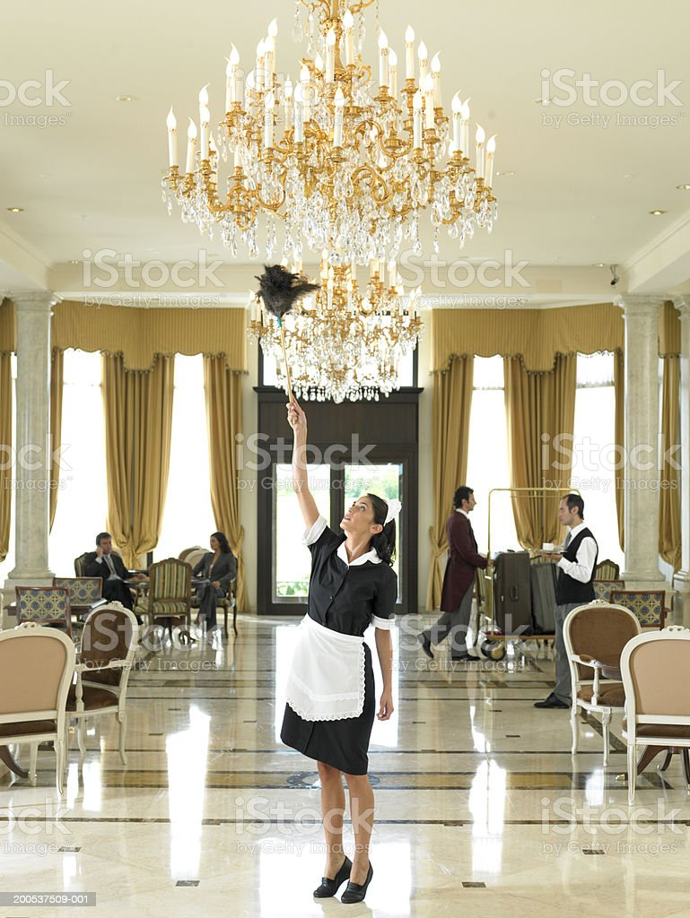 Maid dusting chandelier in hotel foyer royalty-free stock photo