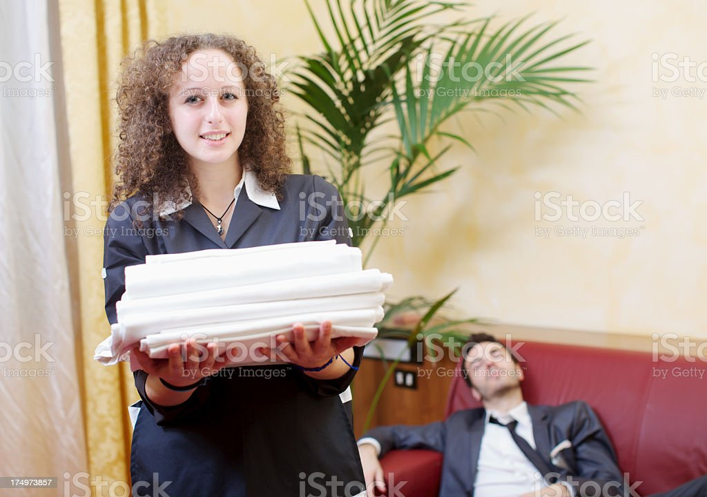 Maid holding stack of towels with sleeping businessman on...