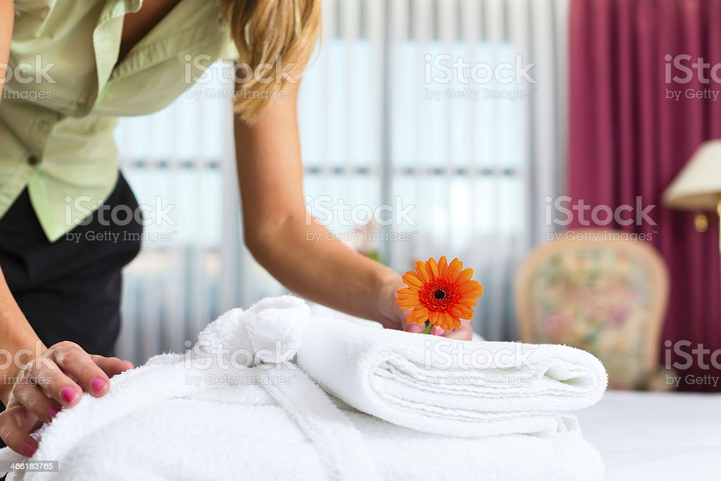 A maid leaving a flower on a towel at a resort hotel stock photo