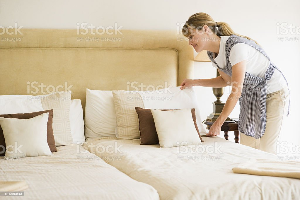Maid making bed in hotel room royalty-free stock photo