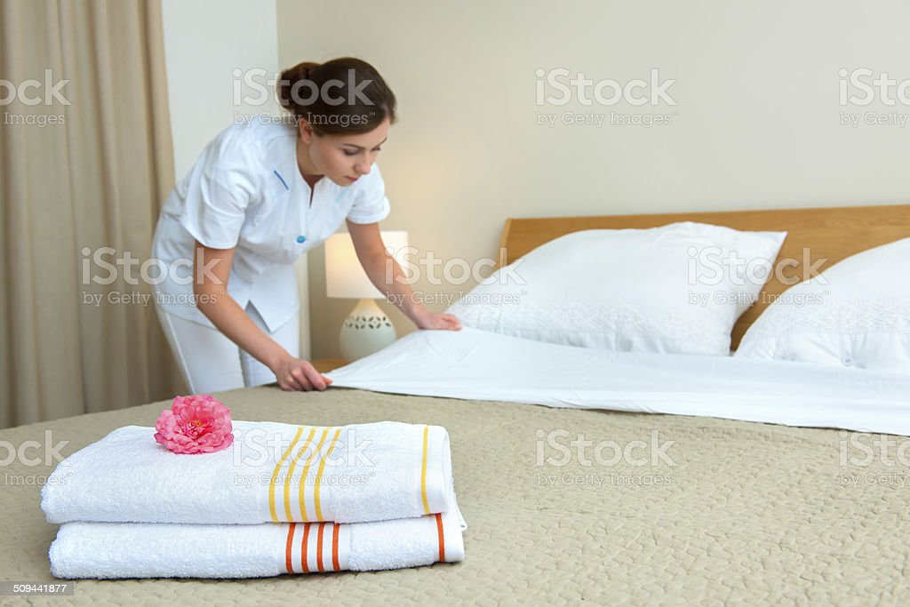 Maid making bed in hotel room Hotel room service. Young maid changing bedclothes in a room Adult Stock Photo