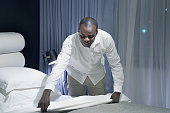 Maid making bed in hotel room. Staff Maid Making Bed. African housekeeper making bed. Toning