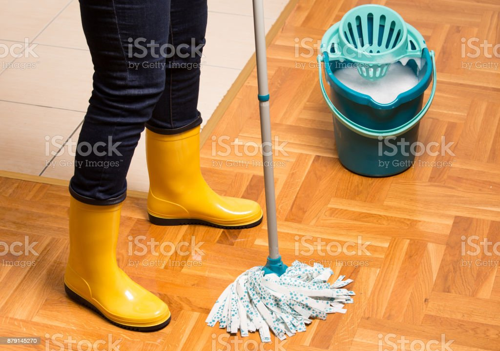 Maid in gumboots mopping parquet floor. Housekeeping and home hygiene...