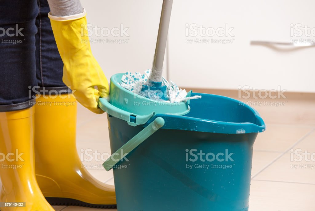 Maid in gumboots squeezing mop in bucket for floor cleaning....