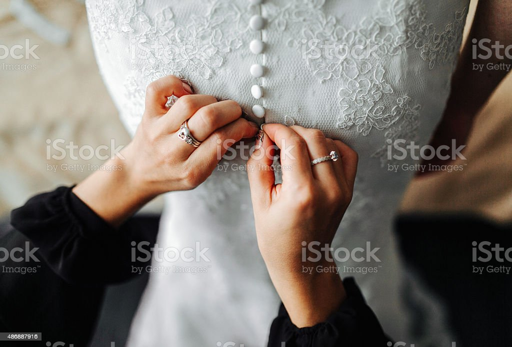 maid of honor helping the bride with her dress stock photo