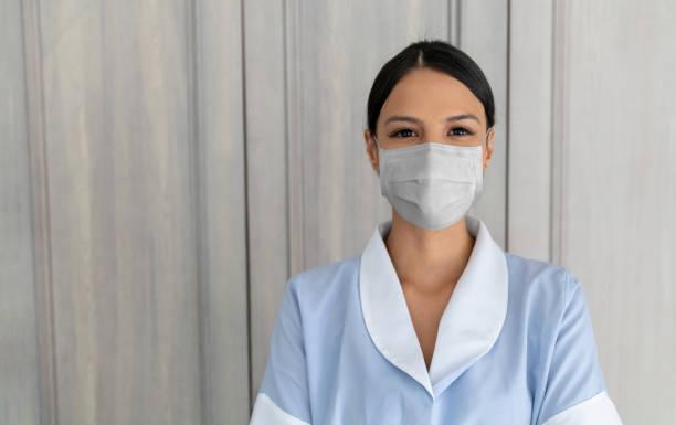 Magd trägt eine Gesichtsmaske, um die Ausbreitung des Coronavirus während der Arbeit in einem Hotel zu vermeiden – Foto