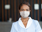 Portrait of an African American maid wearing a facemask to avoid the spread of coronavirus while working at a hotel - Pandemic lifestyle concepts