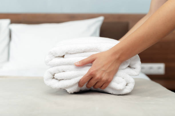 maid with fresh clean towels during housekeeping in a hotel room - maid stock pictures, royalty-free photos & images