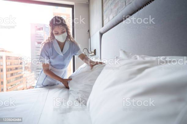 Maid working at a hotel and doing the bed wearing a facemask picture id1225040484?b=1&k=6&m=1225040484&s=612x612&h=miph8fzpvlvp3nwt3gnlpccerdzpyifpq90ajgulon0=