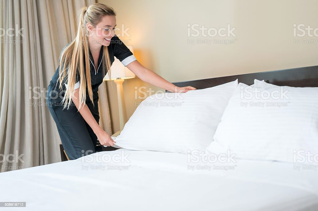 Maid working at a hotel making the bed – Foto
