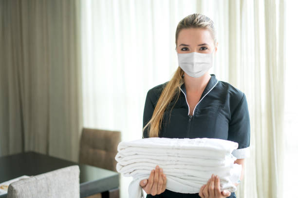 Maid working at a hotel wearing a facemask stock photo