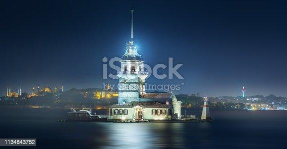 Maiden Tower or Kiz Kulesi in Bosphorus strait at misty night Istanbul, Turkey