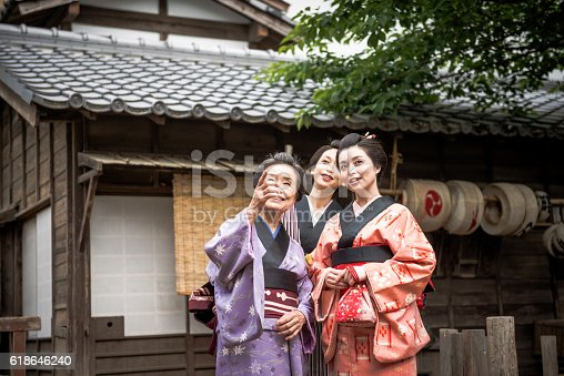 Two young and one elderly Japanese women wearing kimonos and yukatas while walking in traditional Japanese village, followed by Japanese peasants. Image taken with Nikon D800 and developed from RAW in XXXL size, in TOEI studios in Kyoto, Japan