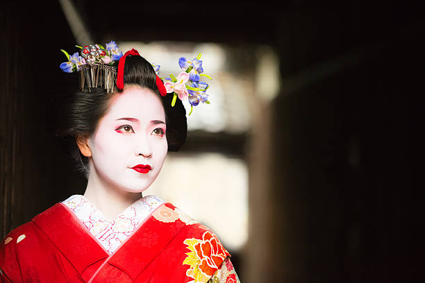 maiko emerging into the light gion kyoto - geisha girl stock photos and pictures