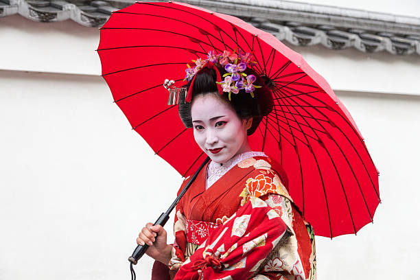 maiko geisha walking on a street in kyoto, japan - geisha girl stock photos and pictures