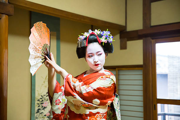 maiko girl dancing with paper fan in japanese tatami room - geisha girl stock photos and pictures
