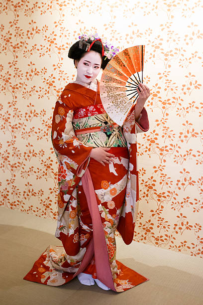 maiko girl posing with japanese folding fan - geisha girl stock photos and pictures