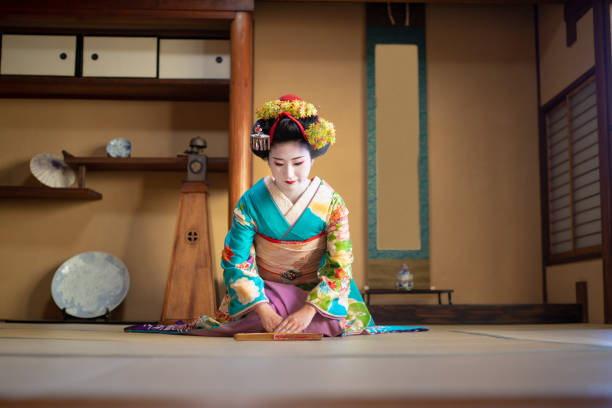Maiko girl sitting on heels and bowing in traditional Japanese tatami room Maiko girl sitting on heels and bowing in traditional Japanese tatami room, Gion, Kyoto geisha stock pictures, royalty-free photos & images