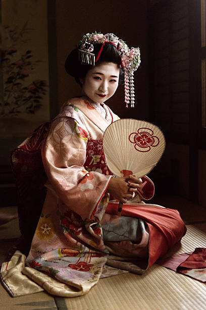 maiko holding a hand fan - geisha girl stock photos and pictures
