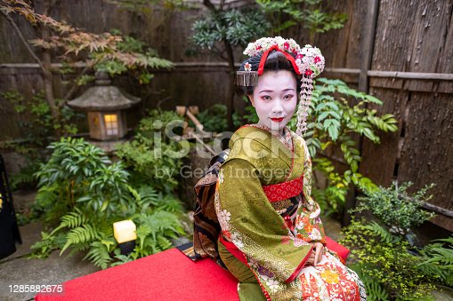 Young female tourist visiting Kyoto in Japan and experiencing Maiko (Geisha in training) makeover.  Wearing traditional Japanese 'Maiko' style kimono with special white face makeup and walking around beautiful city of Kyoto.