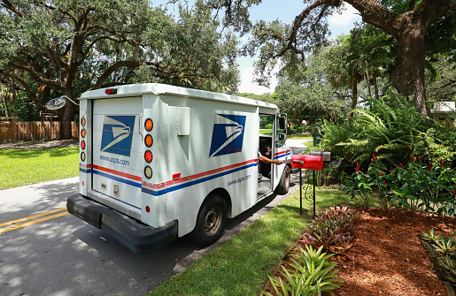 Fort Lauderdale, Florida, USA - September 3, 2020:  Mailman delivering mail in a postal truck puts letters into a red mailbox.