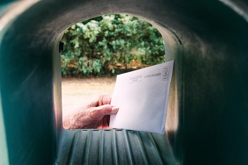 An elderly hand is getting a mail in ballot form out of the mailbox.