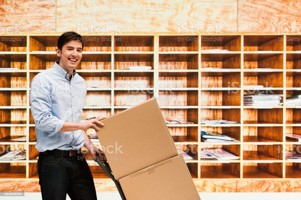 Mail room clerk with boxes for delivery stock photo
