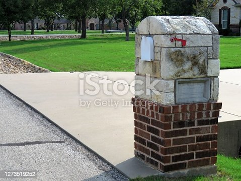 A brick and stone mailbox by a driveway. Copy Space.