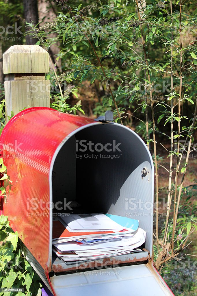 Mailbox Filled with Junk Mail Envelopes and Flyers stock photo