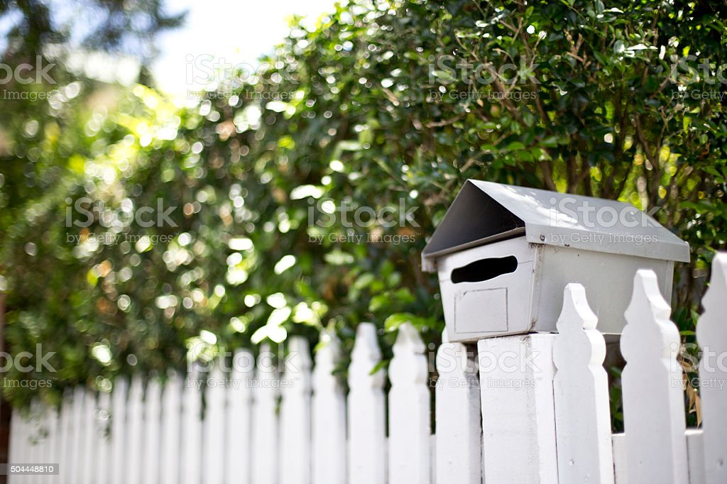 Mailbox on white picket fence stock photo