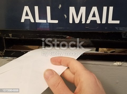 istock Mailing a letter in the post office mail slot 1073984956