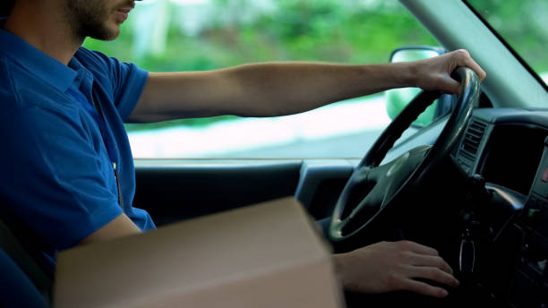 Mailman driving car, cardboard box standing near him, parcels express delivery Mailman driving car, cardboard box standing near him, parcels express delivery samenwerking stock pictures, royalty-free photos & images