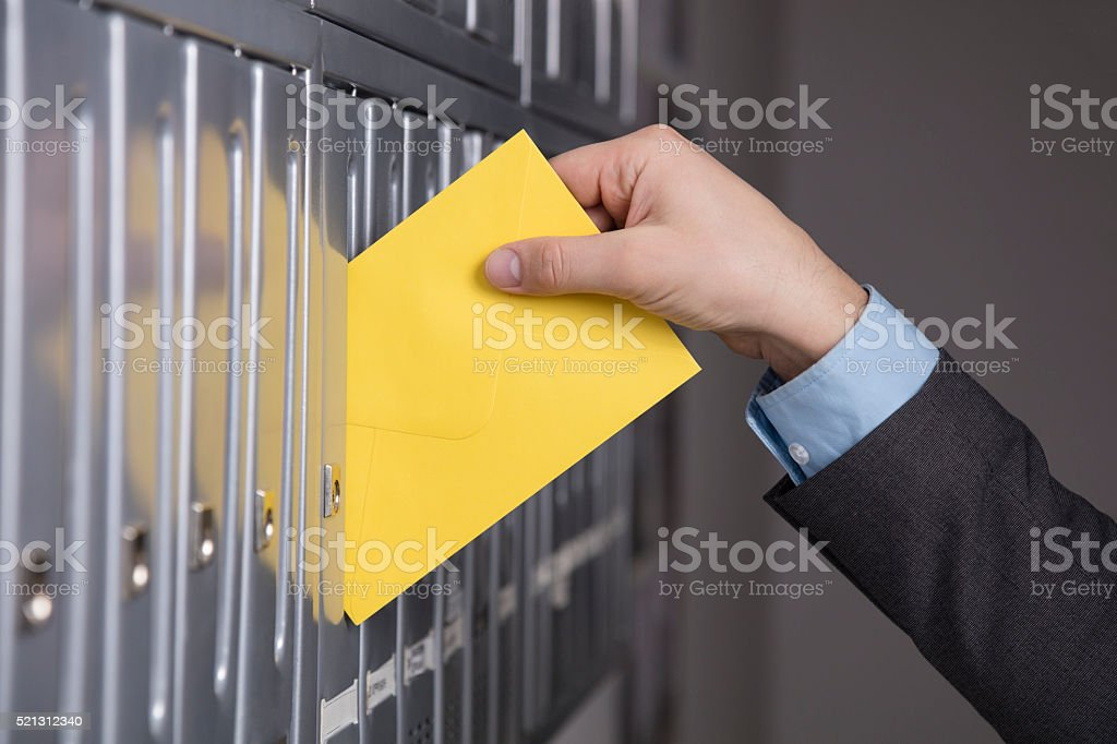 Mailman putting the letter into the mailbox stock photo