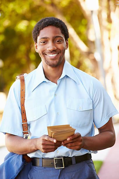 mailman a piedi lungo via offrire lettere - postino foto e immagini stock