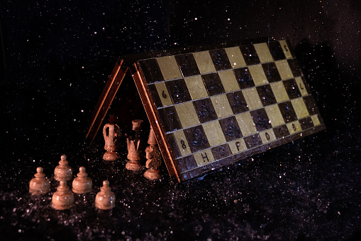 Main chess figures under the game board protecting themselves from the rain in front of the pawns under it, in a dark environment. Concept of society and social class difference