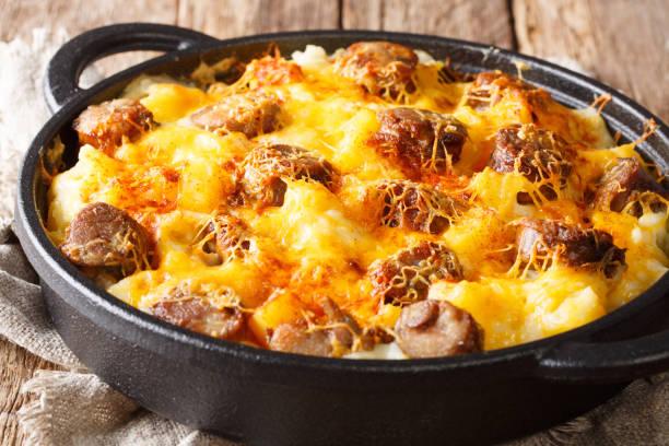 main course from cheese potatoand smoked sausage casserole closeup on the pan. horizontal - caçarola imagens e fotografias de stock