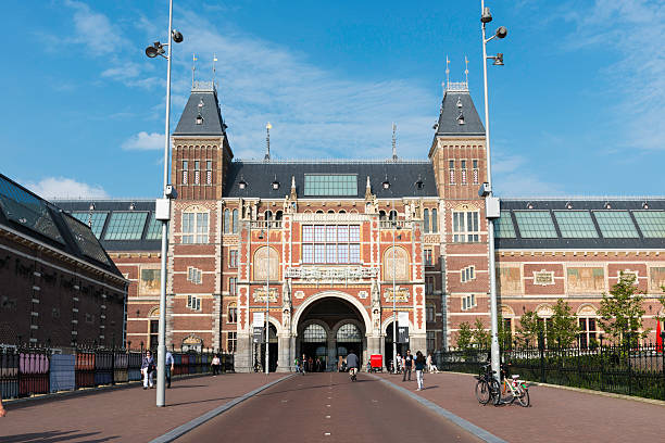 Main facade of the Rijksmuseum in Amsterdam Amsterdam, the Netherlands - September 7, 2014: Locals and tourists passing by the Rijksmuseum (1876-1885) in Amsterdam, the Netherlands, one of the most important museums in the world and home to a vast collection of Dutch art, including painting of Rembrandt, Vermeer and Frans Hall. rijksmuseum stock pictures, royalty-free photos & images