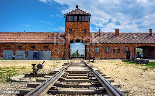 Main gate to nazi concentration camp of Auschwitz Birkenau with train rail, Poland on April 14, 2018.