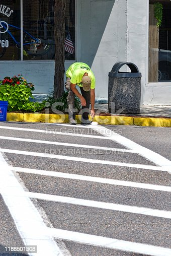 Marion, Virginia - July 19, 2018: A man bends over as he paints a crosswalk using a paint roller on East Main Street in downtown Marion, Virginia, on a hot summer afternoon.
