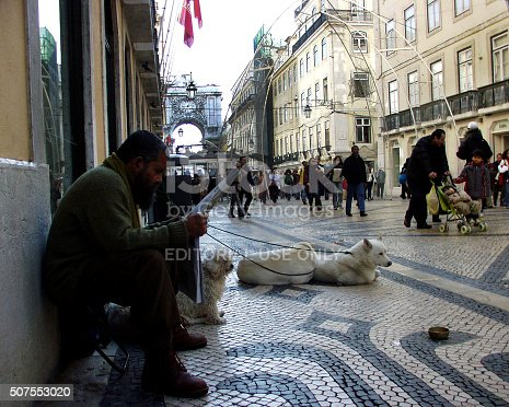 Lisbon, Portugal - January 1, 2005: People walk, sit and enjoy on the Lisbon's main pedestrian street Rua Augusta with a Triumphal Arc with the clock on a warm, beautiful day in January. Famous tram is in the background.