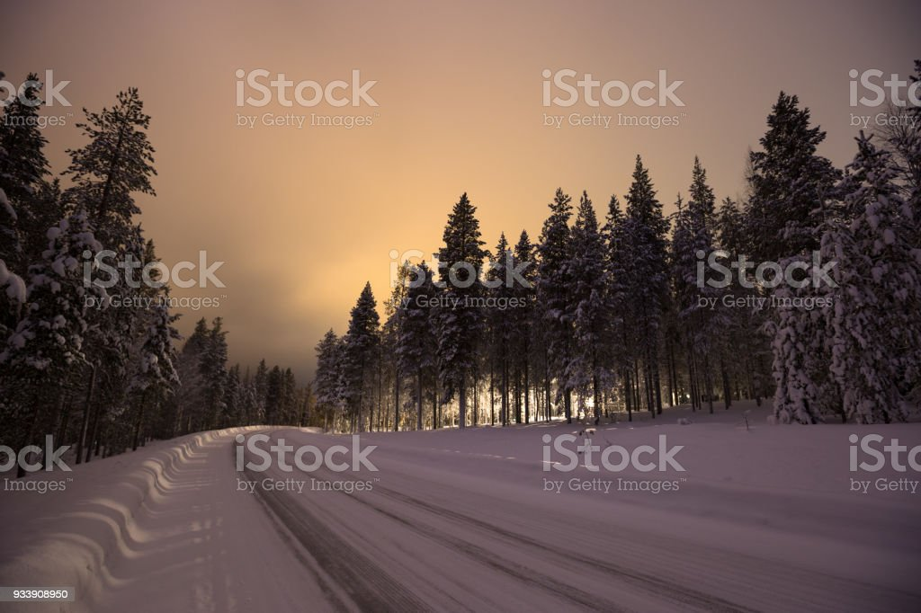 Main road covered in snow with breautiful pre-dawn light in the sky stock photo
