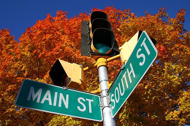 main street im herbst - straßenschild stock-fotos und bilder