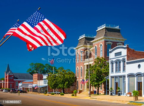 American Flags flying in a small town square.