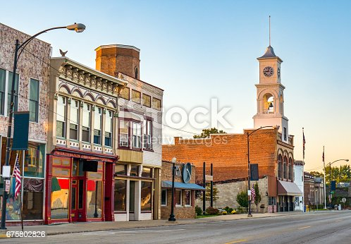 The main street of a quaint, classic small town located in midwestern America with storefronts and a clock tower