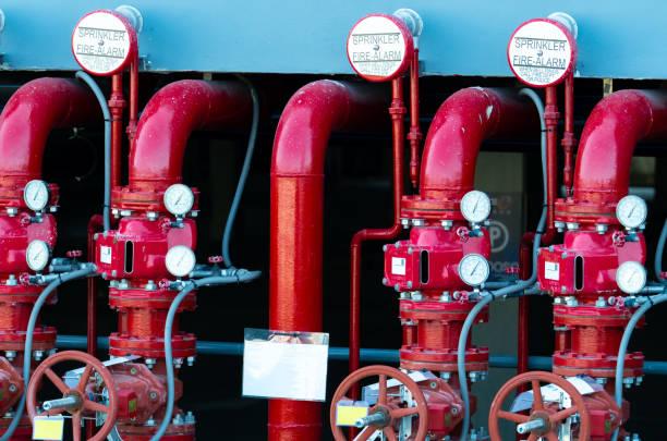 hoofdtoevoer waterleidingen in het brandblussysteem. brand sprinklersysteem met rode pijpen. brand onderdrukking. handmatige afsluiter van brandblussysteem. - exploitatie stockfoto's en -beelden